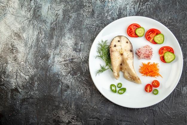 Sopra la vista dei pesci crudi e degli alimenti freschi del pepe sul piatto bianco sul lato sinistro sulla superficie grigia del ghiaccio con spazio libero