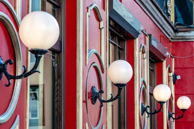 Vista su edificio rosso con lampade a sfera di vetro bianco in fila
