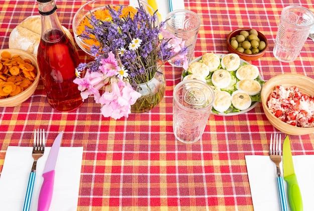Sopra vista della tovaglia a quadretti rossa con antipasti di verdure, forchetta e coltelli.
