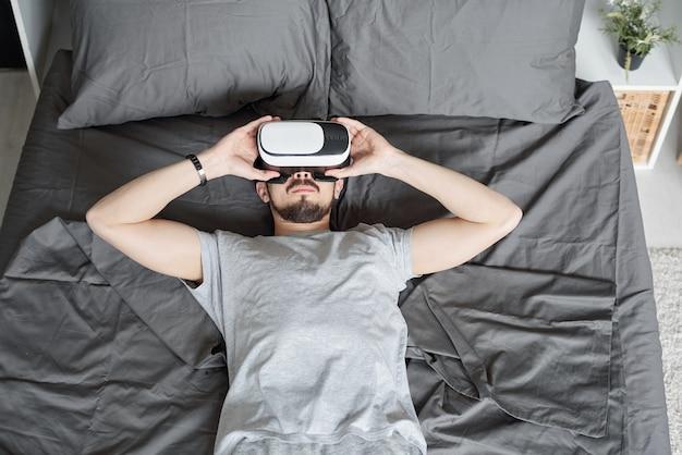 Sopra la vista del giovane barbuto rilassato sdraiato a letto e utilizzando occhiali per realtà virtuale mentre si guarda un film in 3d a casa