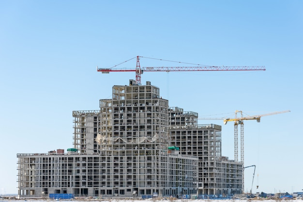 Vista di un complesso residenziale in costruzione con alte gru. edificio su larga scala della città