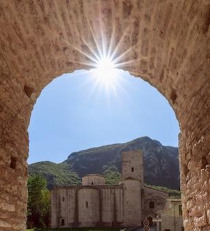 Vista dell'abbazia cattolica romana san vittore alle chiuse dall'arco medievale. genga, marche, italia