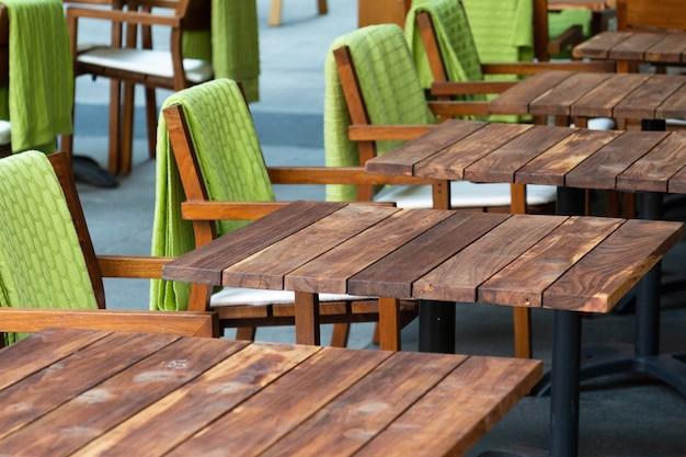 Vista di una fila di tavoli di legno vuoti in un caffè di strada accanto al quale sono sedie con tappeti verdi. città di concetto, caffè, catering, crisi.