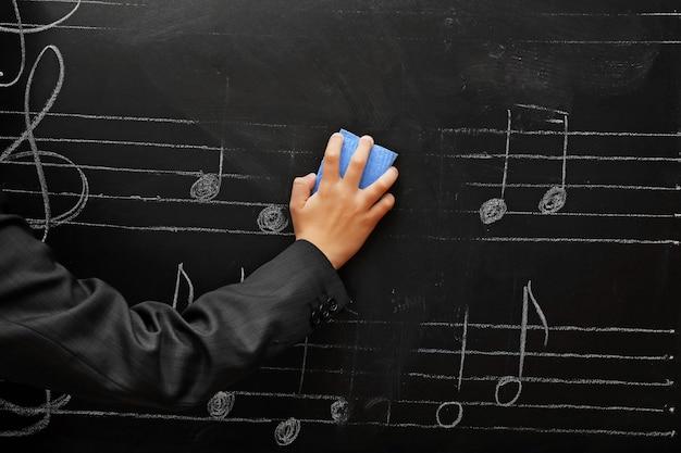 Mostra sulla mano dello scolaro che pulisce la lavagna con note musicali, primo piano