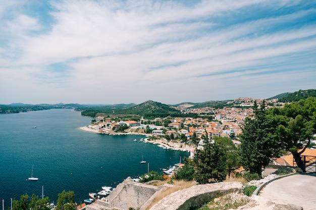 Vista sul mare e sul molo con yacht bianchi da dietro i tetti di vecchie case a lato di sibenik