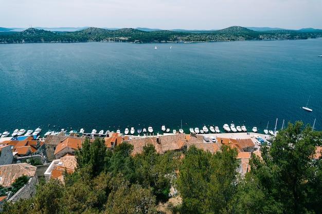 Vista sul mare e sul molo con yacht bianchi da dietro i tetti di vecchie case a sibenik