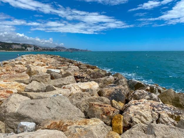 Vista del mare che raggiunge le scogliere nel mar mediterraneo di malaga in estate.