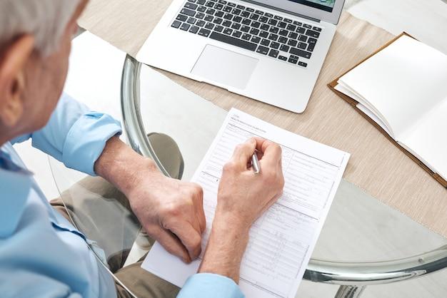 Sopra la vista dell'uomo anziano seduto al tavolo con il laptop e compilando il modulo di assicurazione secondo le istruzioni online