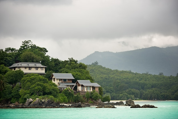 Vista della costa delle seychelles con case nella foresta