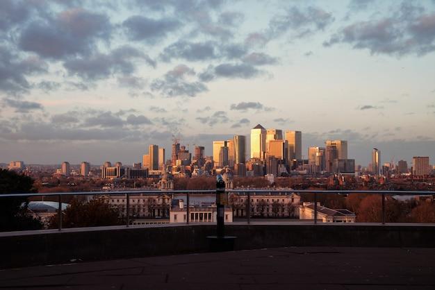 Vista dei grattacieli di londra da un punto di osservazione su greenwich al tramonto e cannocchiale.