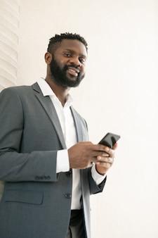 Sotto la vista dell'uomo d'affari barbuto afroamericano sorridente che utilizza il messenger per la comunicazione online sul telefono