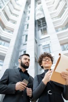 Sotto la vista della giovane imprenditrice sorridente in bicchieri analizzando il piano di vendita con il collega barbuto in ufficio