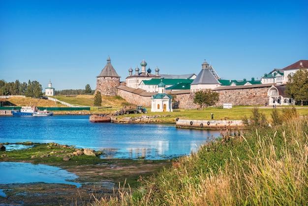 Vista del monastero di solovetsky dalla baia della prosperità e lavori di scarico della legna da ardere dalla nave