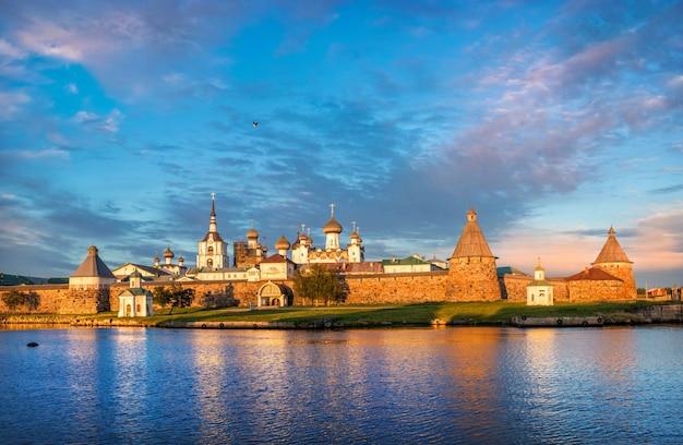 Vista del monastero di solovetsky sulle isole solovetsky con riflesso nell'acqua blu della baia della prosperità sotto i raggi del sole al tramonto