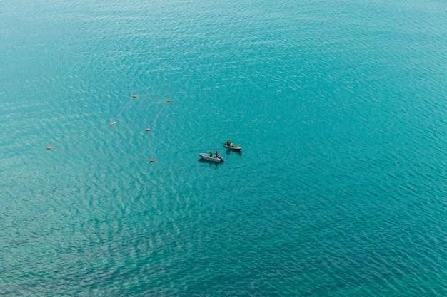 Vista di un motoscafo in movimento. barca con pescatori. i pescatori in barca controllano le reti. trasporto d'acqua e tempo libero estivo.