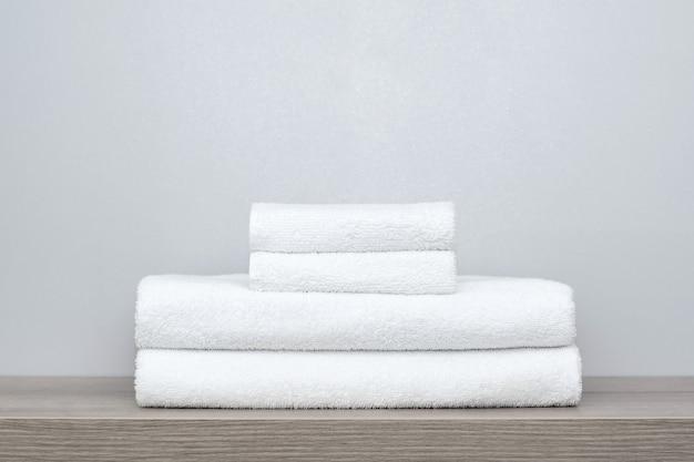 Vista di una pila di asciugamani da bagno bianchi ordinatamente piegati su uno scaffale di legno.