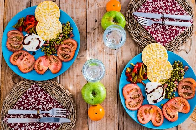 Vista dall'alto del tavolo con due piatti pieni di verdure e cibi dietetici sani su un tavolo in legno alla moda