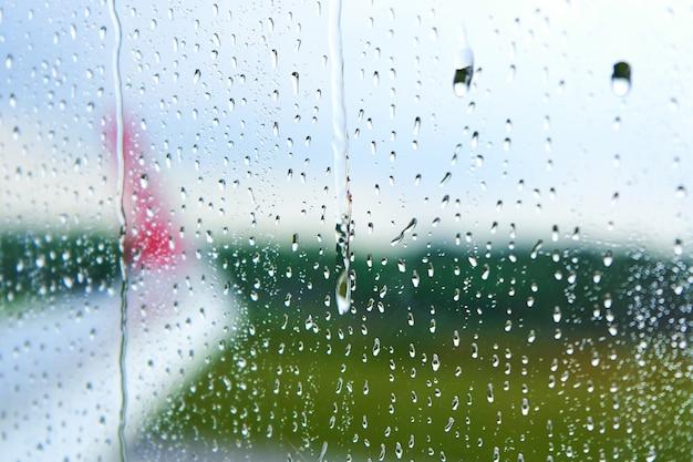 Vista attraverso il vetro appannato di un aereo prima del decollo in una giornata piovosa