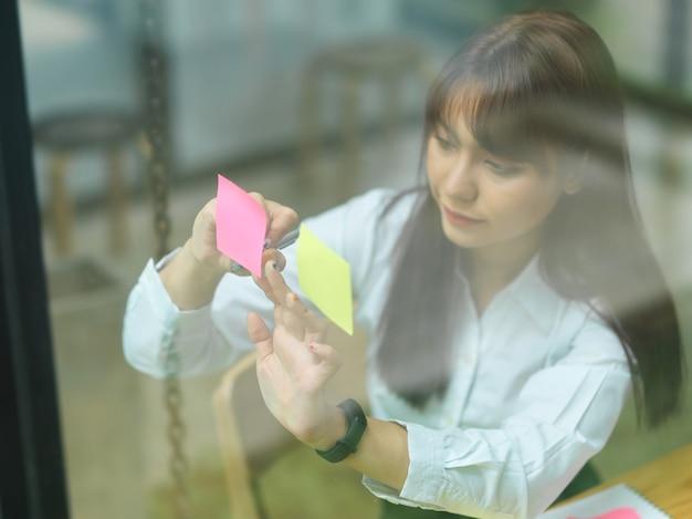 Vista attraverso il vetro business femmina attaccando una nota adesiva strategia di pianificazione su carte colorate