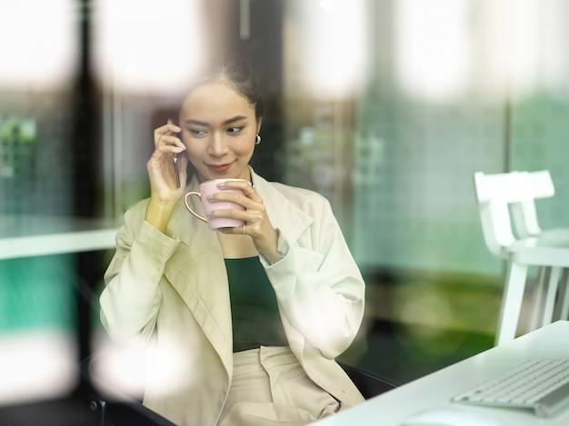 Vista attraverso la finestra di vetro della lavoratrice riposarsi parlando al telefono e pausa caffè sul posto di lavoro