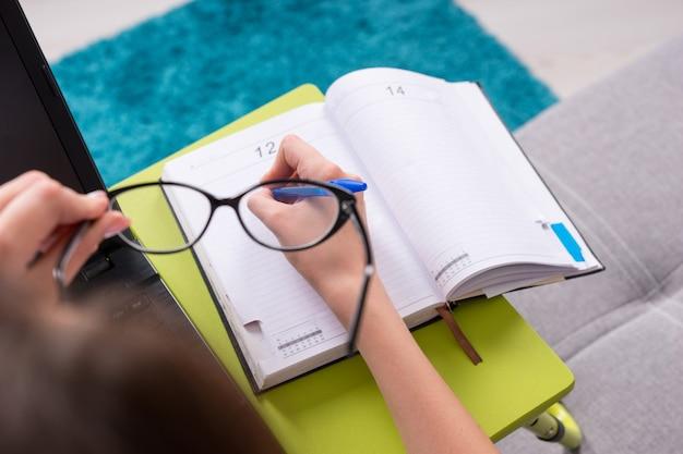 Visualizza attraverso gli occhiali la pagina vuota aperta di un diario o diario aziendale con la mano di una donna, che tiene in mano una penna per fissare appuntamenti, organizzare un programma o un'agenda