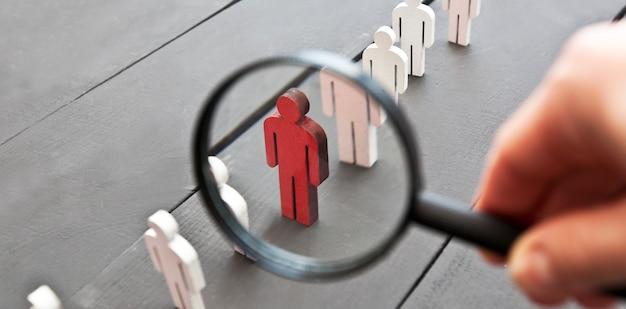 La vista attraverso la lente d'ingrandimento su una persona rossa di legno tra le altre persone
