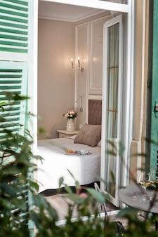 Vista attraverso una porta aperta del balcone verso l'interno della camera da letto