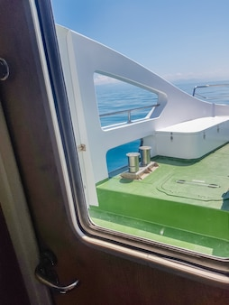 Vista attraverso l'oblò sul ponte di uno yacht di lusso, primo piano.