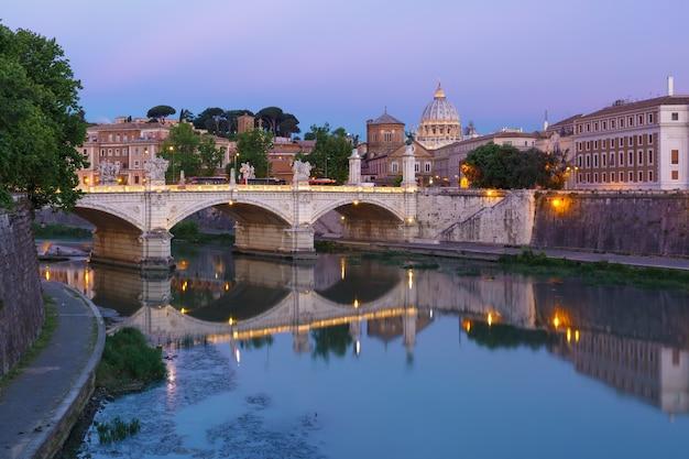 Vista del fiume tevere, del ponte vittorio emanuele ii e della cattedrale di san pietro durante l'ora blu mattutina a roma, italia.