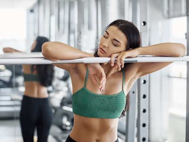 Vista della ragazza stanca dopo il sollevamento pesi. donna in palestra dopo un duro allenamento posa con la testa