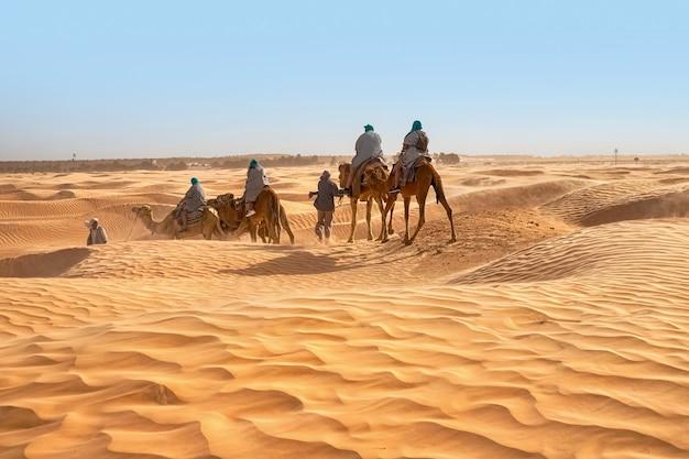 Vista di turisti che cavalcano cammelli nel deserto del sahara durante forti venti