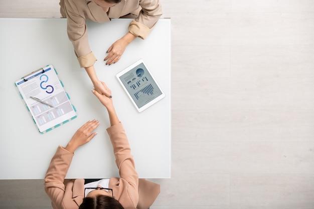 Vista di due giovani imprenditrici contemporanee che si stringono la mano sulla scrivania dopo aver fatto un accordo tra le informazioni finanziarie su tablet e su carta