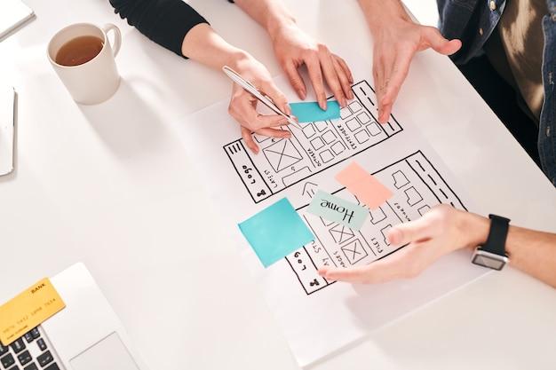Sopra la vista dei progettisti dell'interfaccia utente che discutono del nuovo design dell'interfaccia per smartphone e offrono idee diverse