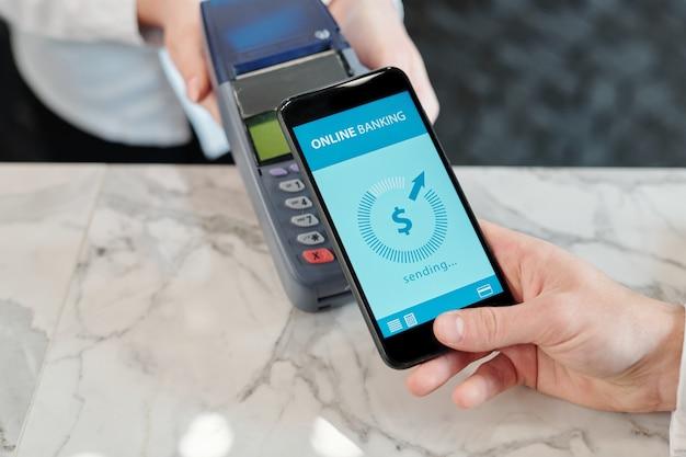 Vista in alto di un cliente irriconoscibile che mette lo smartphone sul terminale durante l'utilizzo del pagamento nfc alla reception dell'hotel