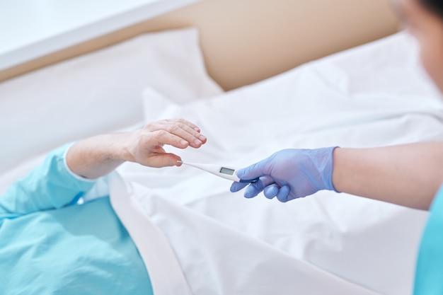 Sopra la vista di un'infermiera irriconoscibile in guanti chirurgici che dà termometro digitale al paziente a letto