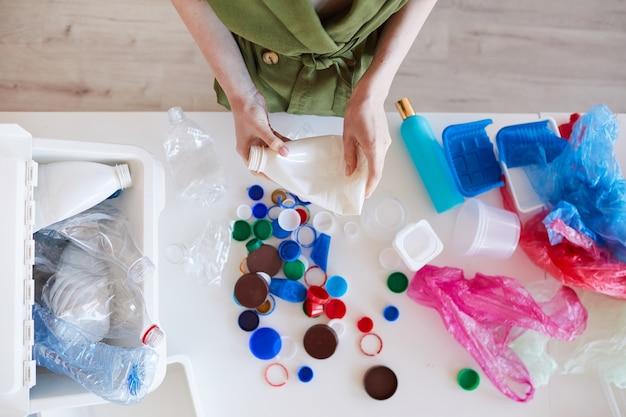 Sopra la vista di una giovane donna irriconoscibile che ordina i rifiuti di plastica a casa prima del riciclaggio