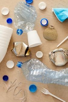 Sopra la vista di vari elementi della spazzatura disposti in una composizione minima su cartone, raccolta differenziata e concetto di riciclaggio