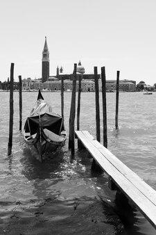 Vista di venezia con la singola gondola attraccata e la chiesa di san giorgio di maggiore, italia. immagine in bianco e nero