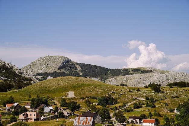 Vista del villaggio in montagna sullo sfondo del cielo e del verde