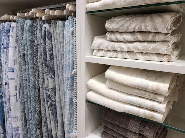 Vista di un armadio con coperte di lana appese a grucce e asciugamani di spugna sugli scaffali.