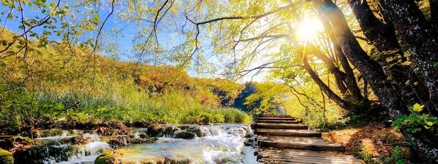 Vista delle cascate e del pontone al sole nel parco nazionale di plitvice, croazia