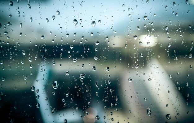 Vista su strada bagnata in un giorno di pioggia attraverso la finestra con gocce d'acqua