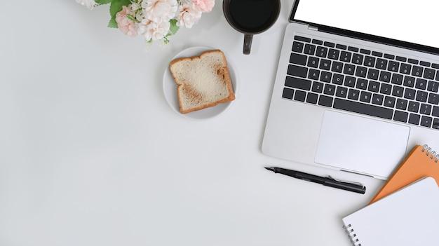 Vista dall'alto scrivania da ufficio bianca con computer portatile, notebook, pane e tazza di caffè.