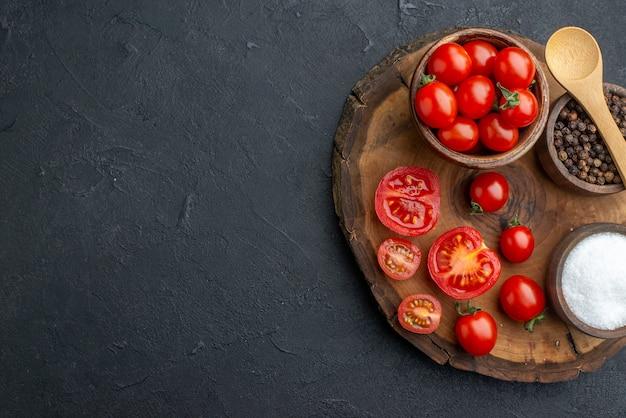 Sopra la vista di pomodori e spezie freschi interi tagliati su tavola di legno sul lato sinistro su superficie nera con spazio libero