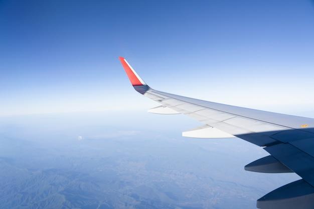 Vista dell'aereo dell'ala con paesaggio del cielo blu