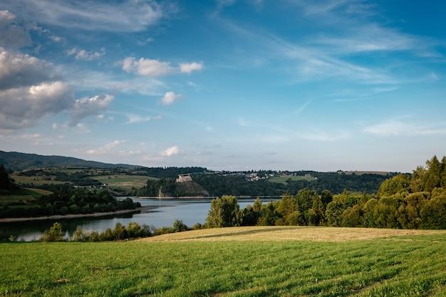 Vista con carreggiata asfaltata, prati con erba verde, montagne, cielo azzurro con nuvole e sole.