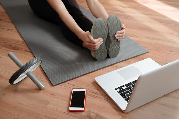 Vista di una donna che conduce una lezione di fitness virtuale a casa durante una videoconferenza