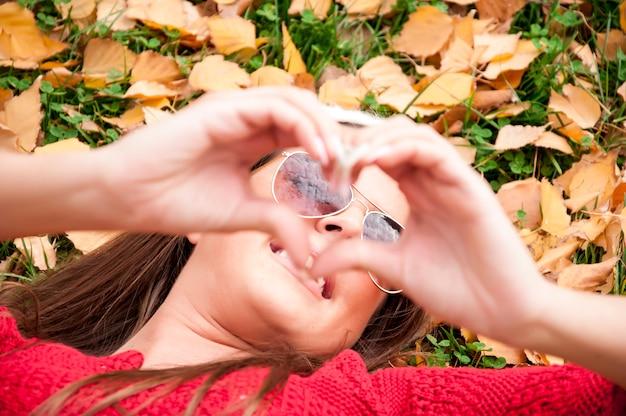 La vista della mano della donna che fa un cuore modella con le sue dita nel parco mentre si posa sul g