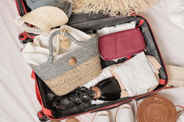 Sopra la vista della roba da donna imballata nella valigia sul letto, preparandosi prima delle vacanze estive