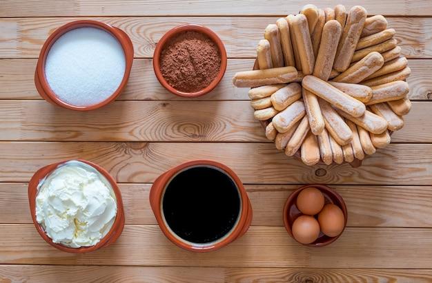 Sopra vista di un tavolo in legno con ingredienti per preparare un tiramisù fatto in casa